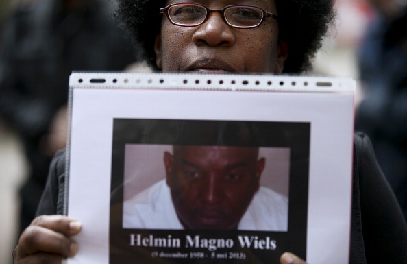A woman holds a portrait of Helmin Wiels as she takes part in a protest event on May 11, 2013, in Rotterdam, in honor of the late popular leader of Curacao's largest political party who was shot dead on May 5. Approximately 300 people took part in the gathering. Gunmen on May 5 fired at least six shots at Helmin Wiels, 54, as he was having an afternoon drink with friends at a beach about three kilometres (1.6 miles) southeast of Willemstad. Wiels was the leader of Curacao's largest political party, Pueblo Soberano and was an outspoken supporter of full independence for Curacao, an autonomous island which still partly falls under control of the Netherlands. AFP PHOTO / ANP / JERRY LAMPEN ***Netherlands out*** (Photo credit should read JERRY LAMPEN/AFP/Getty Images)
